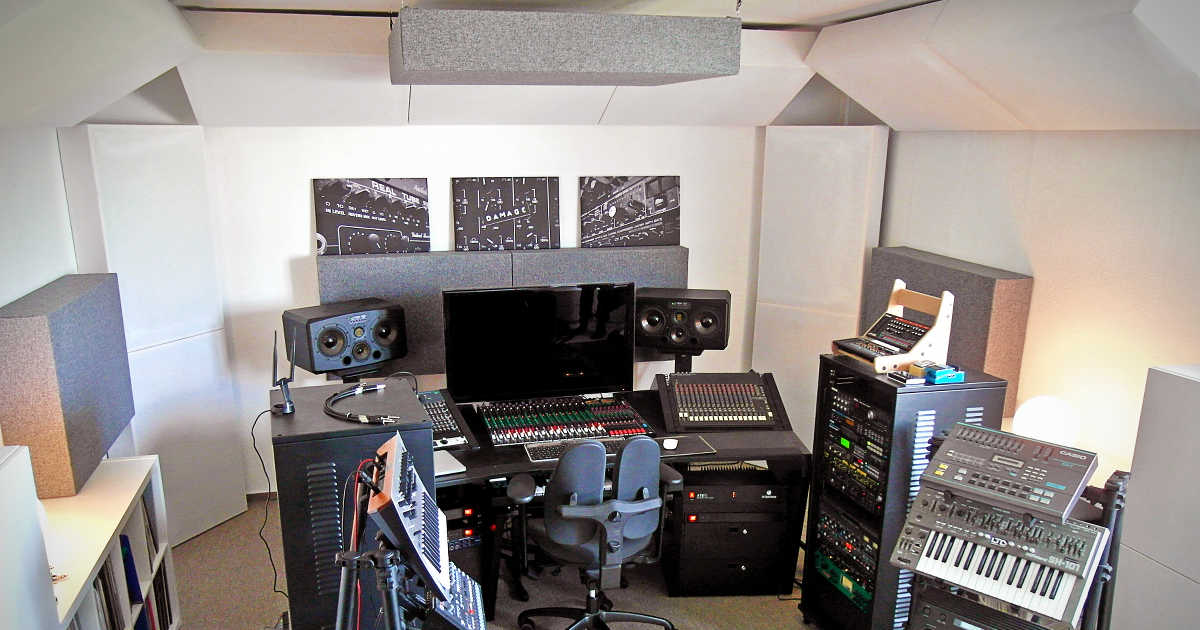 project studio with a workstation desk, several outboard units and acoustic absorbers in the corners.
