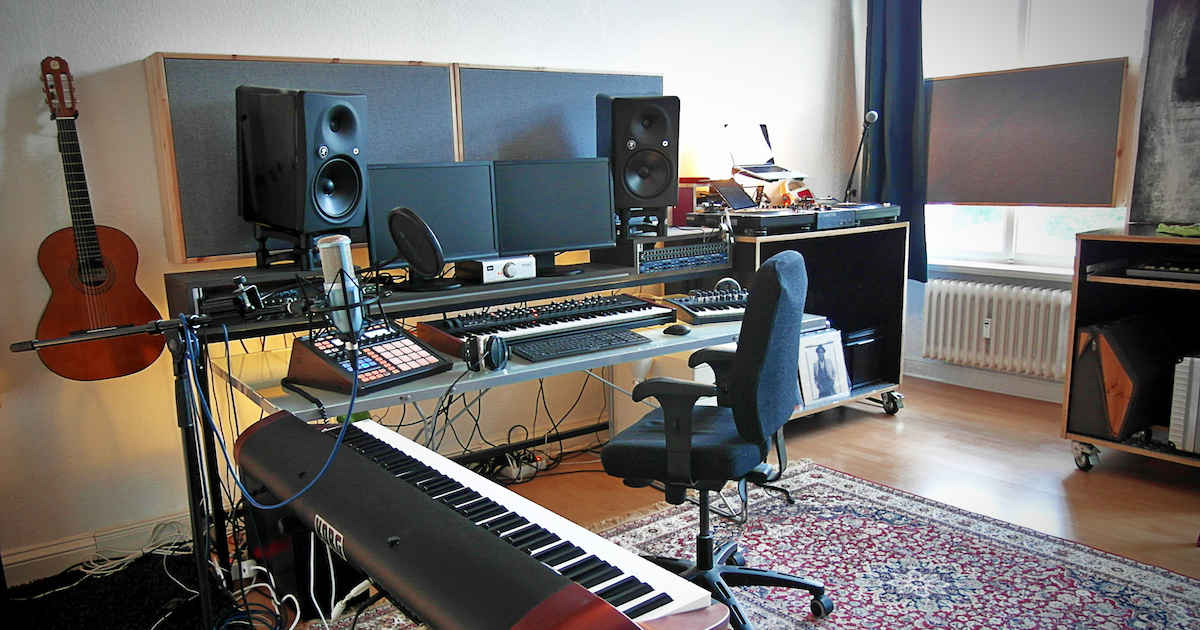 home studio work station with a piano in the front and a guitar on the wall.