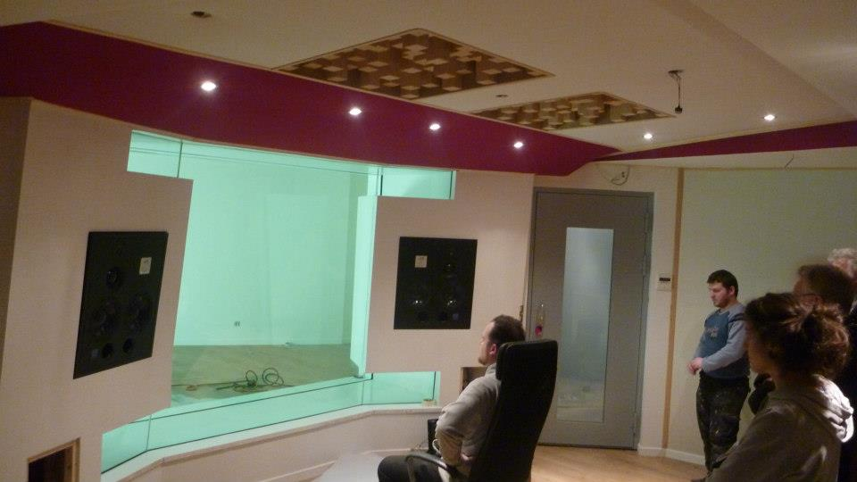 person sitting in a chair in front of 2 large speakers suspended in glass